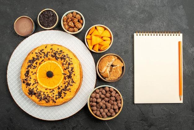 어두운 표면 비스킷 과일 디저트 파이 케이크 차에 오렌지 조각과 플레이크가 있는 상위 뷰 맛있는 파이