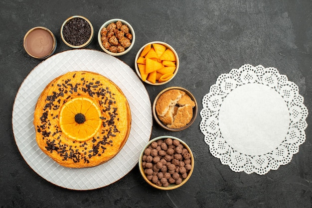 Top view delicious pie with orange slices and flakes on dark surface biscuit fruit dessert pie cake tea