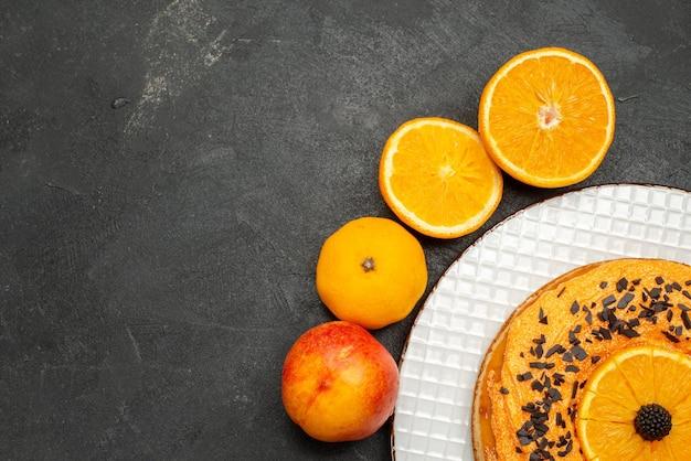 어두운 표면 과일 디저트 파이 케이크 비스킷 차에 오렌지 조각을 넣은 상위 뷰 맛있는 파이