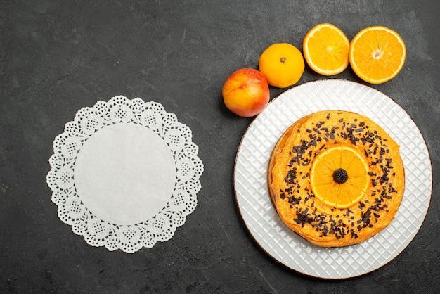 トップビューダークデスクフルーツデザートパイケーキビスケットティーにオレンジスライスとおいしいパイ