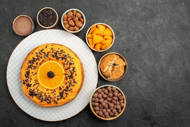 暗い表面にオレンジのスライスが付いたトップビューのおいしいパイビスケットフルーツデザートパイケーキティー