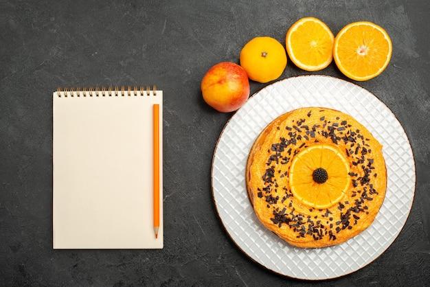 暗い表面にオレンジスライスが入ったトップビューのおいしいパイフルーツデザートパイケーキビスケットティー