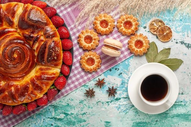Torta deliziosa vista dall'alto con fragole e tazza di tè sulla superficie blu