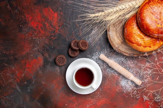 Vista dall'alto deliziose torte per una tazza di tè su torte di pasticceria torta dolce tavolo scuro