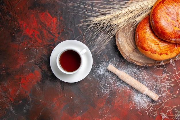 ダークテーブルの甘いケーキペストリーパイのお茶のトップビューおいしいパイ