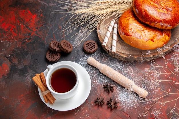 暗いテーブルの上のお茶のトップビューおいしいパイ