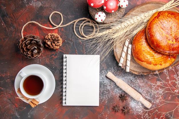 暗いテーブルの上のお茶とおいしいパイの上面図甘いケーキペストリーパイ
