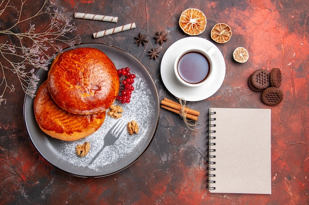 トップビューダークデスクの甘いケーキペストリーパイにお茶とおいしいパイ