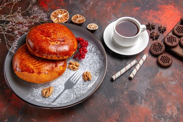 暗い机の上のお茶と甘いパイケーキペストリーの上面図おいしいパイ