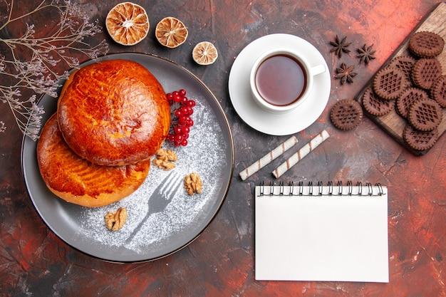 トップビューダークテーブルの甘いパイペストリーケーキにお茶とおいしいパイ