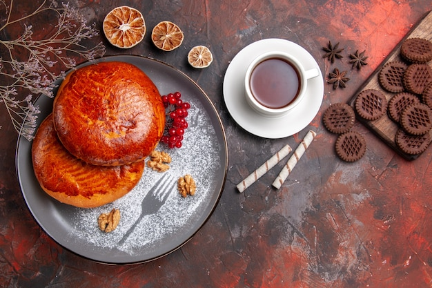 暗いテーブルの上のお茶とおいしいパイの上面図甘いパイケーキペストリー