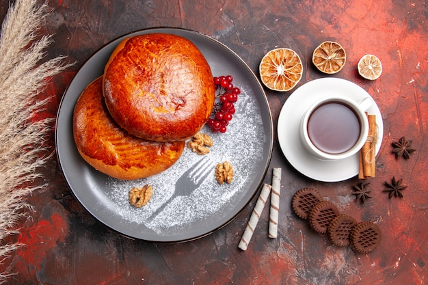 トップビューダークテーブルスイーツパイペストリーケーキにお茶とおいしいパイ