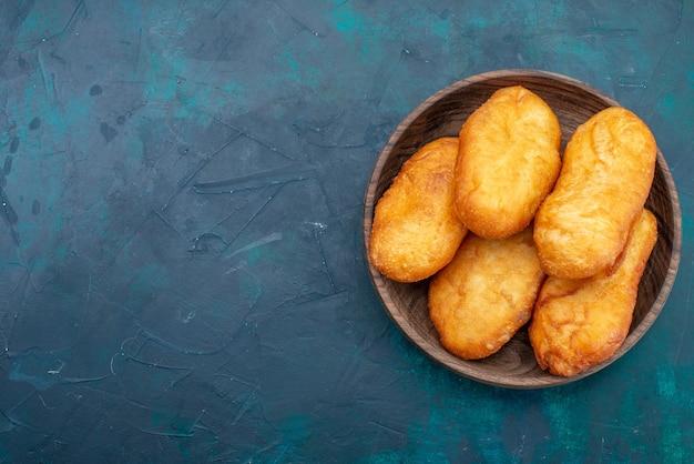 Вид сверху вкусные пироги с мясной начинкой внутри тарелки на темно-синем фоне, тесто, пирог, хлеб, булочка, еда