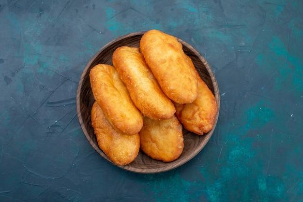 Вид сверху вкусные пироги с мясной начинкой внутри деревянной тарелки на темно-синем фоне, тесто, пирог, хлеб, булочка, еда