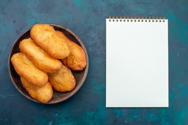 濃紺の背景にメモ帳付きの木製プレートの内側に肉が詰まったおいしいパイの上面図生地パイパンパン食品