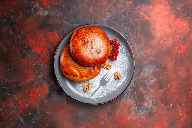 Vista dall'alto deliziose torte con bacche rosse sulla torta di pasticceria torta dolce tavolo scuro