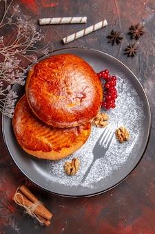 Вид сверху вкусные пироги с красными ягодами на темном столе сладкий пирог из теста