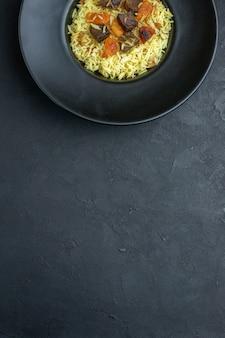 上面図暗い表面のプレートの内側にドライアプリコットと肉のスライスが入ったおいしいピラフ炊き込みご飯