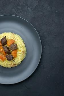 어두운 표면에 접시 안에 말린 살구와 고기 조각이있는 상위 뷰 맛있는 필라프 밥