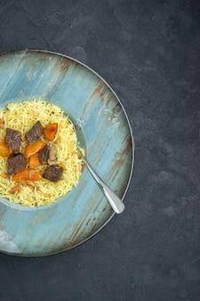 Vista dall'alto delizioso riso cotto pilaf con albicocche secche e fette di carne all'interno del piatto sulla superficie scura