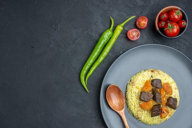 Вид сверху вкусный плов приготовленный рис с ломтиками мяса и помидорами на темной поверхности