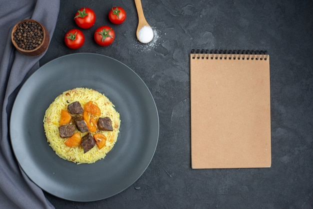Vista dall'alto delizioso riso cotto pilaf con fette di carne e pomodori sulla superficie scura