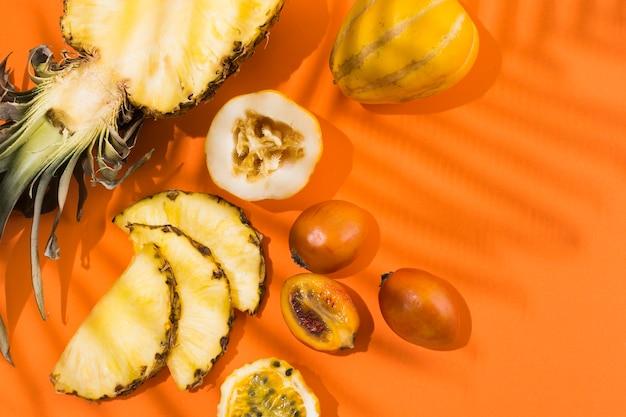 Вид сверху вкусного ананаса и фруктов на столе