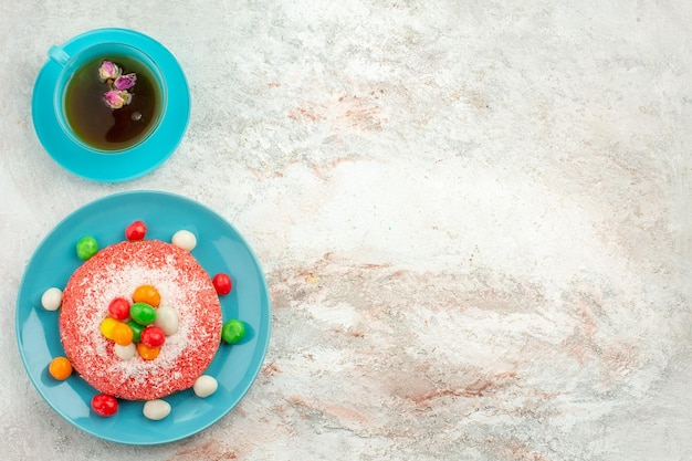 Top view delicious pink cake with colorful candies and cup of tea on white surface pie rainbow color cake dessert candy