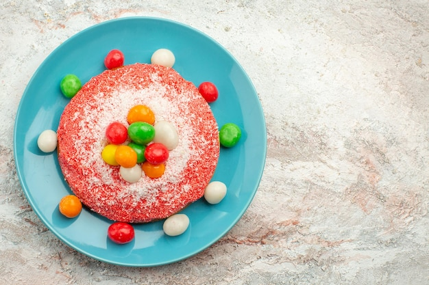Top view delicious pink cake with colorful candies inside plate on the white surface rainbow candy color pie cake dessert
