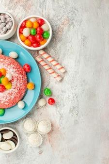 上面図白い表面にカラフルなキャンディーとおいしいピンクのケーキ虹色のデザートケーキキャンディー