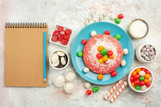 上面図白い机の上のカラフルなキャンディーとおいしいピンクのケーキ虹色のデザートケーキキャンディー