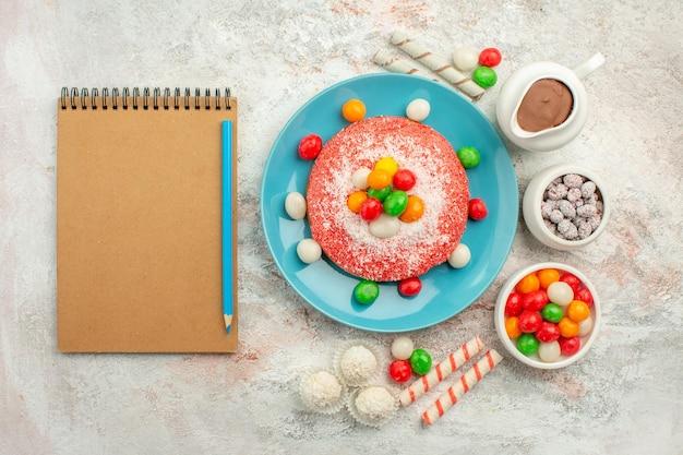 上面図白い表面にカラフルなキャンディーが付いたおいしいピンクのケーキデザートカラーグッディーレインボーケーキキャンディー