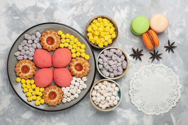トップビュー白い机の上にキャンディーとクッキーとおいしいピンクのケーキ甘いケーキビスケットティーパイクッキー
