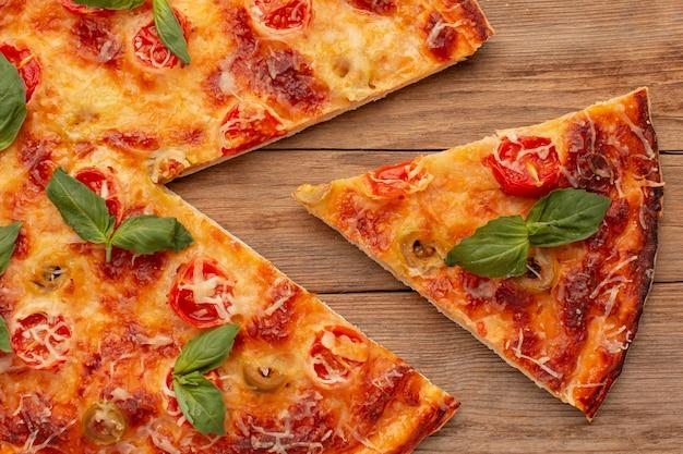 木製の背景においしいピザの上面図