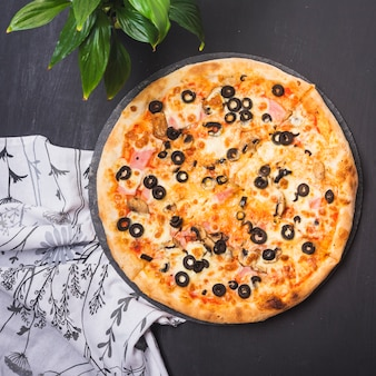 Top view of delicious pizza on slate with plant and garments