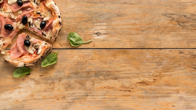 Top view of delicious pizza with basil leaf over wooden desk
