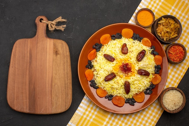 Top view delicious plov with different raisins on a dark space