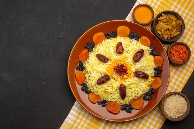 Top view delicious plov with different raisins on dark space