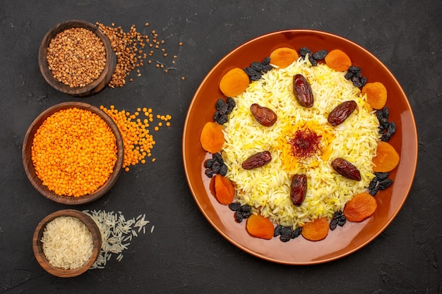Top view delicious plov with different raisins on the dark space