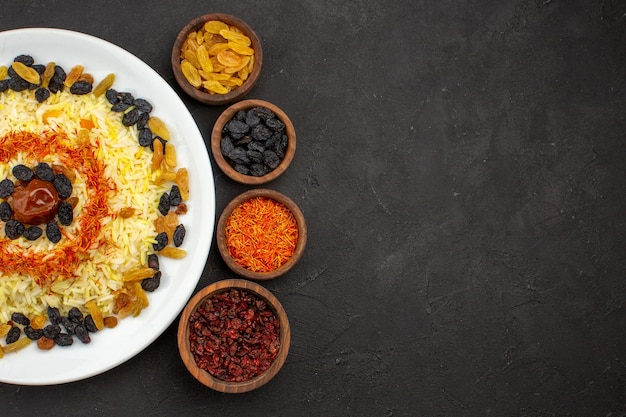 Top view delicious plov with different raisins inside plate on dark desk