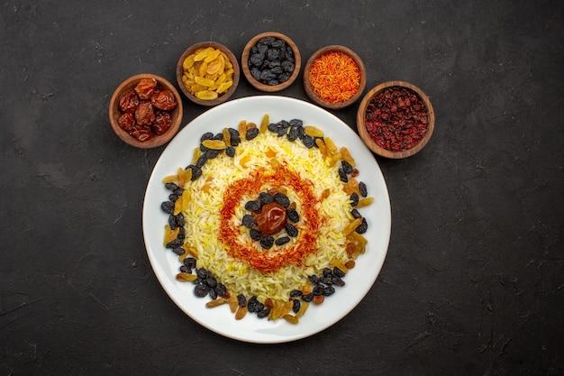 Vista dall'alto delizioso plov con uvetta diversa all'interno del piatto nello spazio buio