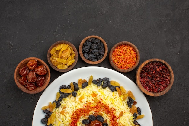 Top view delicious plov with different raisins inside plate on dark space