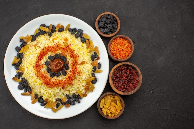 Top view delicious plov with different raisins inside plate on the dark space