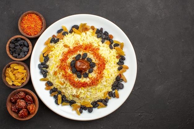 Vista dall'alto delizioso plov con olio e uvetta all'interno del piatto nello spazio buio