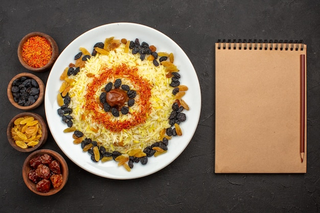 Top view delicious plov with oil and raisins inside plate on dark space