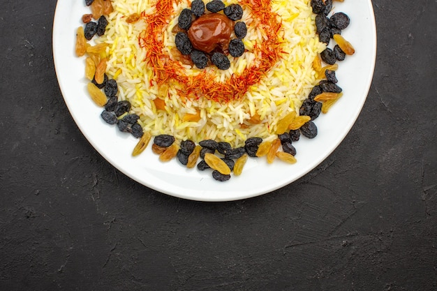 Top view delicious plov with oil and raisins inside plate on the dark space