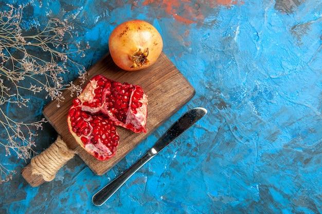Vista dall'alto deliziose melagrane sul tagliere del coltello da pranzo su sfondo blu