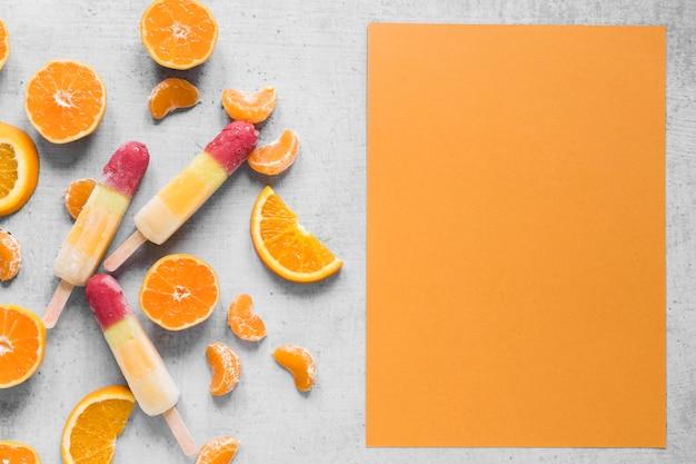 Vista dall'alto di deliziosi ghiaccioli con arancia e copia spazio