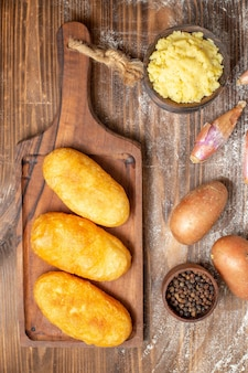 上面図木製の机の上にマッシュポテトとおいしいポテトホットケーキを焼くケーキペッパー生地の色