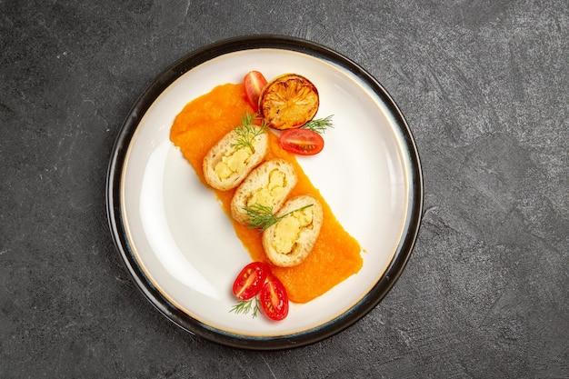 灰色の背景のオーブン焼き色皿ディナースライスのプレートの内側にカボチャが付いている上面図おいしいポテトパイ